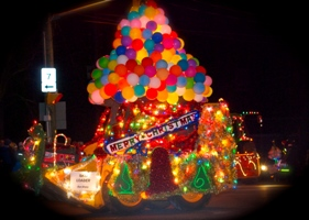 A photo of a float with lights and balloons at the Parade of Lights