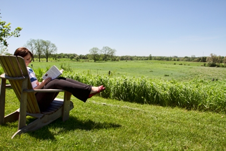 Photo of a young woman reading a book in a wooden chair by a green field in summer