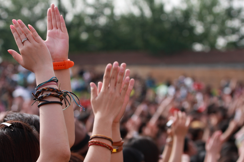 A crowd of hands clapping along to music at a festival